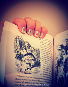 Hand with fingernails that spell R-E-A-D holding Alice in Wonderland book